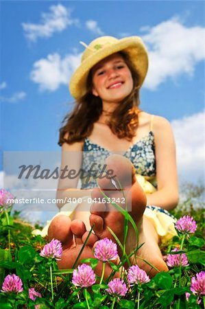 Young teenage girl sitting on summer meadow amid wildflowers in straw hat Stock Photo - Budget Royalty-Free, Image code: 400-04163242
