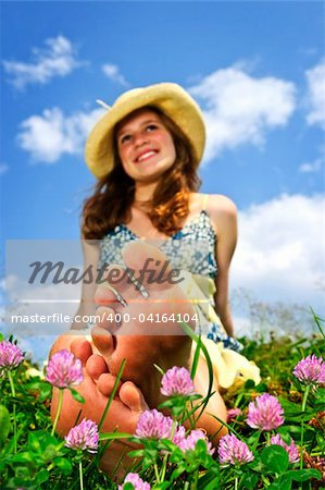Young teenage girl sitting on summer meadow amid wildflowers in straw hat Stock Photo - Budget Royalty-Free, Image code: 400-04164104