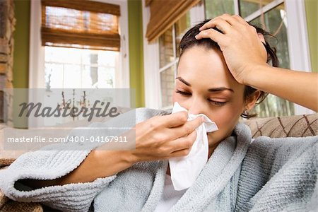 Sick young woman blows her nose into a tissue. Horizontal shot. Stock Photo - Budget Royalty-Free, Image code: 400-04167911