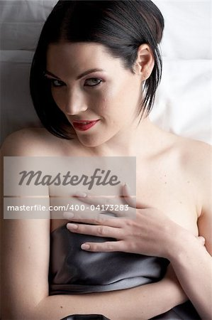 Sexy naked young caucasian adult woman with red lips, short black hair and a pierced eyebrow, covered in a dark satin sheet and sitting on a bed Stock Photo - Budget Royalty-Free, Image code: 400-04173283