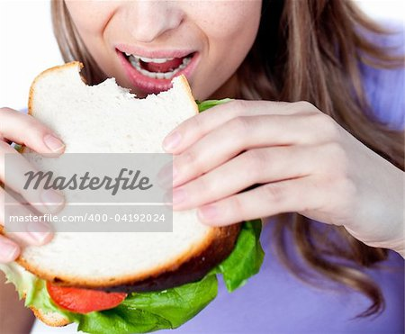 Close-up of a woman eating a sandwich isolated on a white background Stock Photo - Budget Royalty-Free, Image code: 400-04192024