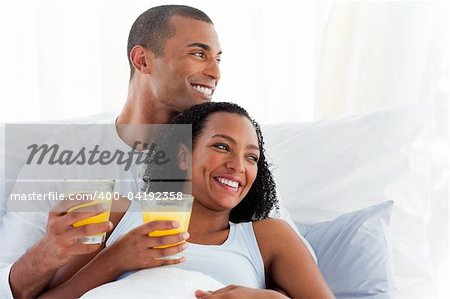 Romantic couple drinking orange juice lying on their bed Stock Photo - Budget Royalty-Free, Image code: 400-04192358
