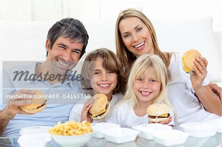 Happy family eating hamburgers sitting on the floor at home Stock Photo - Budget Royalty-Free, Image code: 400-04193348
