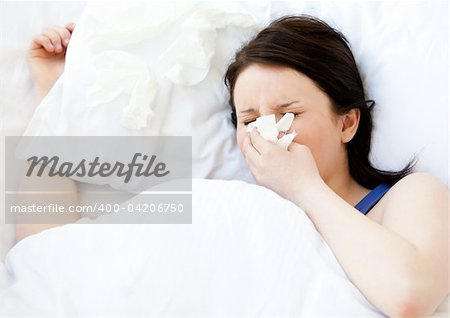 Sick young woman using a tissue lying in a bed at home Stock Photo - Budget Royalty-Free, Image code: 400-04206750