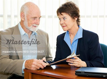 Senior man and his agent or broker having a serious discussion before he signs paperwork. Stock Photo - Budget Royalty-Free, Image code: 400-04208627