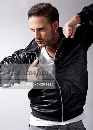 Smart male model giving movement with black jacket on a isolated grey background Stock Photo - Budget Royalty-Free, Image code: 400-04209220
