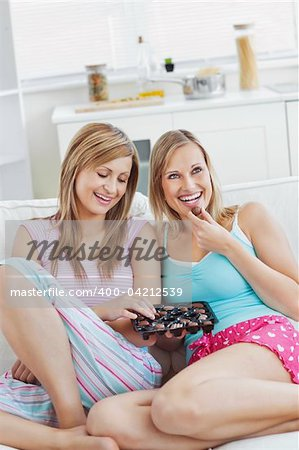 Two smiling women eating chocloate together on a sofa at home Stock Photo - Budget Royalty-Free, Image code: 400-04212539