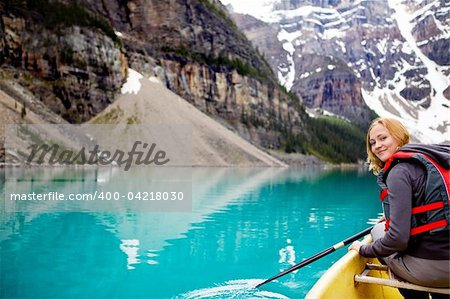 A woman canoeing on Moraine Lake, a tight crop with copy space