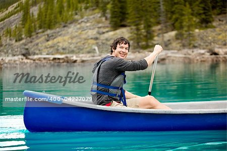 A portrait of a smiling man in a canoe on a glacial lake