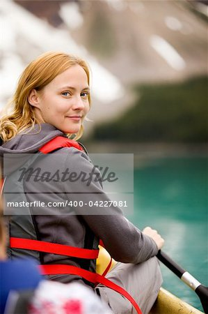 A portrait of a smiling woman in a canoe on a glacial lake. Stock Photo - Royalty-Free, Artist: Leaf, Code: 400-04227081