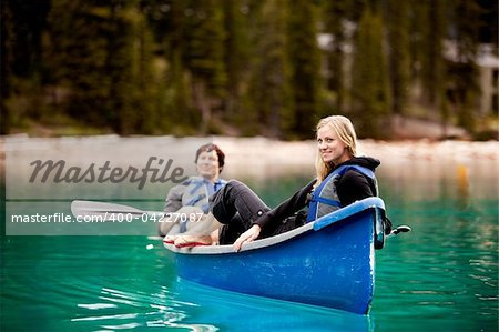 A happy couple relaxing in a canoe on a glacial lake