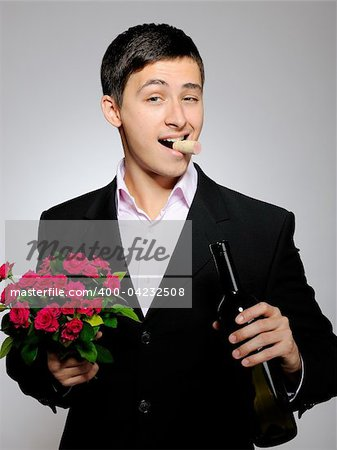 Handsome romantic young man holding rose flower and vine bottle  prepared for a date. gray background Stock Photo - Budget Royalty-Free, Image code: 400-04232508