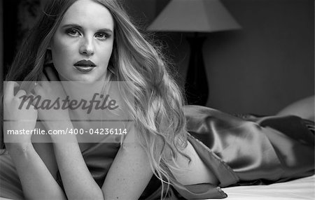 Sexy naked young caucasian adult woman with blonde hair lying on a bed, covered with a dark silk sheet. Single light source, Black and White Stock Photo - Budget Royalty-Free, Image code: 400-04236114