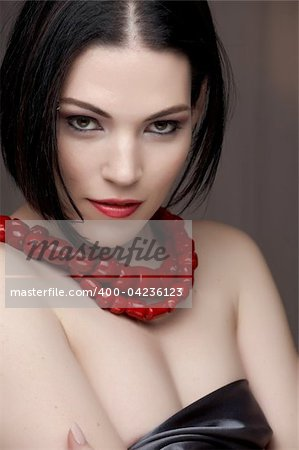 Sexy young caucasian adult woman with red lips, short black hair and a pierced eyebrow, covered in a dark satin sheet and wearing a red coral necklace Stock Photo - Budget Royalty-Free, Image code: 400-04236123