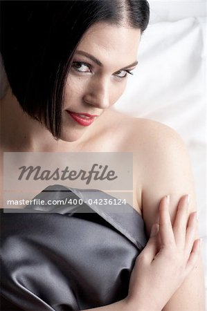Sexy naked young caucasian adult woman with red lips, short black hair and a pierced eyebrow, covered in a dark satin sheet and sitting on a bed Stock Photo - Budget Royalty-Free, Image code: 400-04236124