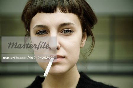 real young woman smokes on the street, selective focus Stock Photo - Budget Royalty-Free, Image code: 400-04262900