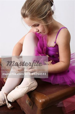 Young girl tying over sized pointe shoes dreaming of becoming a ballerina Stock Photo - Budget Royalty-Free, Image code: 400-04264593