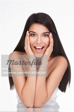 a portrait of a young woman, posing on a white background. she has her elbows on a white table and her hands on her face. she has a surprised expression on her face. Stock Photo - Budget Royalty-Free, Image code: 400-04266260