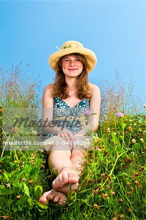Young teenage girl sitting on summer meadow in straw hat Stock Photo - Budget Royalty-Free, Image code: 400-04268254