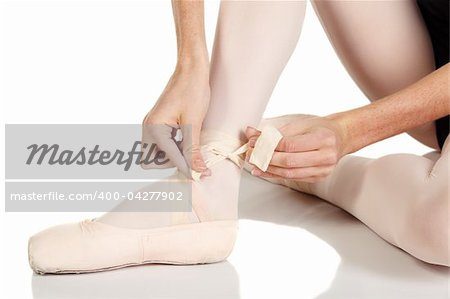 Young caucasian ballerina girl on white background and reflective white floor tying her ballet shoes. Not Isolated Stock Photo - Budget Royalty-Free, Image code: 400-04277902