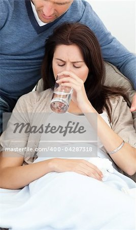 Sick woman drinking water lying on the sofa with her boyfriend Stock Photo - Budget Royalty-Free, Image code: 400-04287318