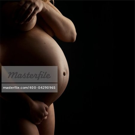 Naked pregnant woman on black background, on the late stage of her pregnancy Stock Photo - Budget Royalty-Free, Image code: 400-04290965