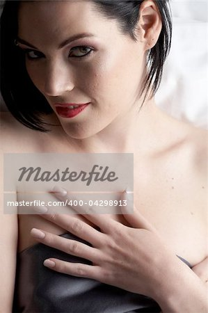 Sexy naked young caucasian adult woman with red lips, short black hair and a pierced eyebrow, covered in a dark satin sheet and sitting on a bed Stock Photo - Budget Royalty-Free, Image code: 400-04298913