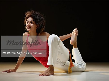 portrait of young adult latin american female doing yoga exercise in gym. Horizontal shape, full length, side view, copy space Stock Photo - Budget Royalty-Free, Image code: 400-04318322