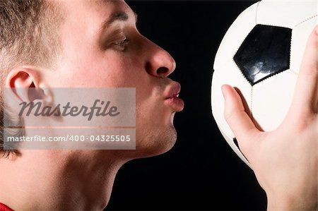 soccer player is kissing the ball in dark Stock Photo - Budget Royalty-Free, Image code: 400-04325505