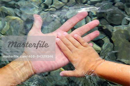 adult and children hands holding underwater wavy distorted Stock Photo - Budget Royalty-Free, Image code: 400-04329346