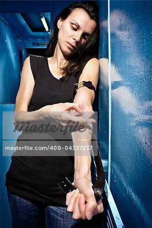 Skinny girl is drug addict. Alone in elevator she takes heroin drug. Stock Photo - Budget Royalty-Free, Image code: 400-04337237