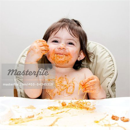 Happy smiling baby having fun eating messy covered in Spaghetti Angel Hair Pasta red marinara tomato sauce. Stock Photo - Budget Royalty-Free, Image code: 400-04345319