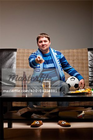 soccer fan is sitting on sofa with beer at home Stock Photo - Budget Royalty-Free, Image code: 400-04358881