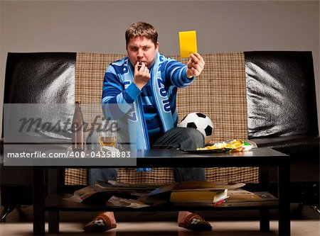 soccer fan is sitting on sofa with beer and showing yellow card at home Stock Photo - Budget Royalty-Free, Image code: 400-04358883