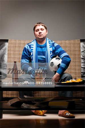 soccer fan is sitting on sofa with beer at home Stock Photo - Budget Royalty-Free, Image code: 400-04358885