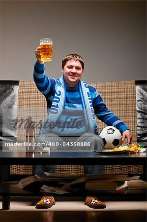 soccer fan is sitting on sofa with beer at home Stock Photo - Budget Royalty-Free, Image code: 400-04358886