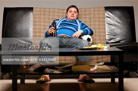 soccer fan is sitting on sofa with beer at home Stock Photo - Budget Royalty-Free, Image code: 400-04358887