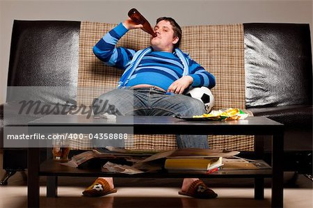 soccer fan is sitting on sofa with beer at home Stock Photo - Budget Royalty-Free, Image code: 400-04358888