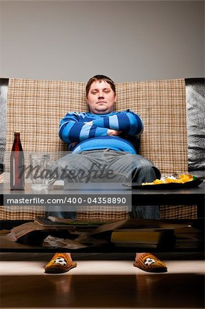 soccer fan is sitting on sofa with beer at home Stock Photo - Budget Royalty-Free, Image code: 400-04358890