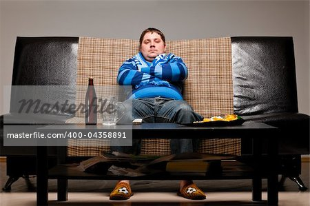 soccer fan is sitting on sofa with beer at home Stock Photo - Budget Royalty-Free, Image code: 400-04358891
