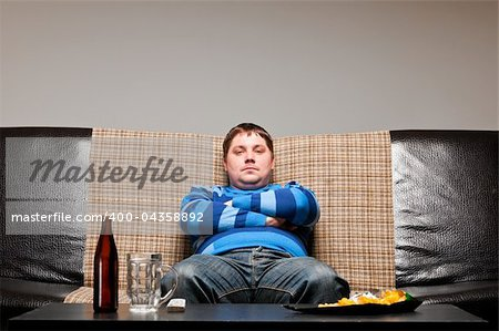 soccer fan is sitting on sofa with beer at home Stock Photo - Budget Royalty-Free, Image code: 400-04358892
