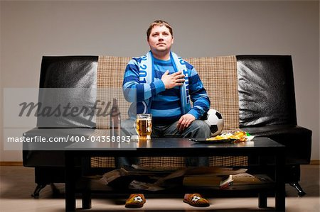 soccer fan is sitting on sofa and listening for a hymn with beer at home Stock Photo - Budget Royalty-Free, Image code: 400-04358893