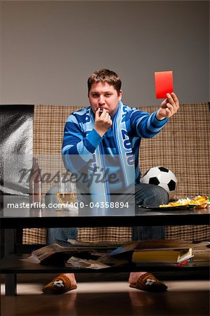 soccer fan is sitting on sofa with beer and showing red card at home Stock Photo - Budget Royalty-Free, Image code: 400-04358894