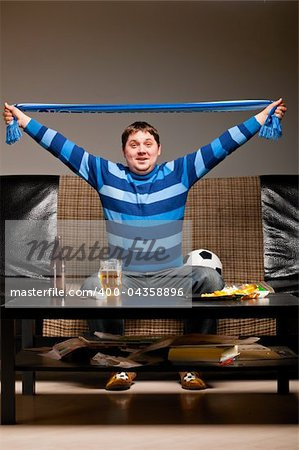 soccer fan is sitting on sofa with beer at home and holding scarf. Stock Photo - Budget Royalty-Free, Image code: 400-04358896