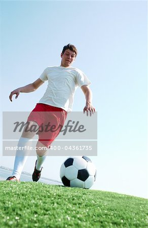 Portrait of a soccer player going to kick ball on football field Stock Photo - Budget Royalty-Free, Image code: 400-04361735