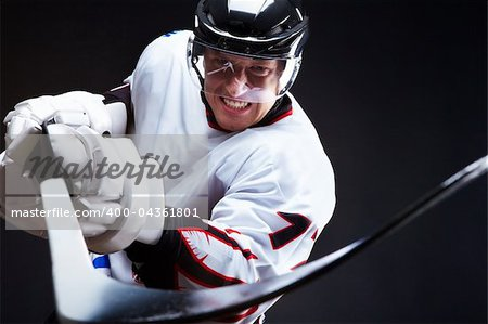 Angry ice-hockey player pointing stick into opponent