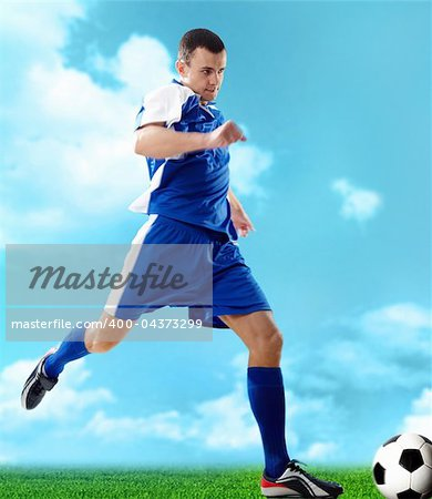 Portrait of a soccer player with ball on a blue background Stock Photo - Budget Royalty-Free, Image code: 400-04373299