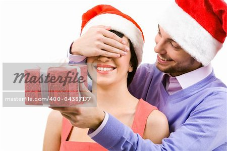Portrait of happy man closing female?s eyes by his hand while holding giftbox before her Stock Photo - Budget Royalty-Free, Image code: 400-04387177