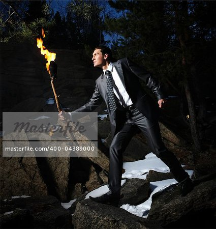 Image of elegant man holding burning stick while moving in darkness