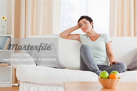 Smiling woman sitting on a sofa in her living room Stock Photo - Budget Royalty-Free, Image code: 400-04410545